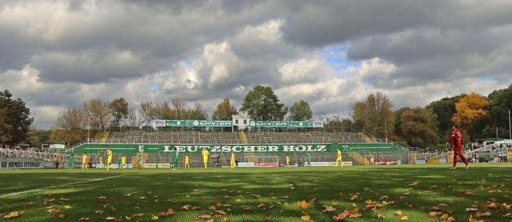 Ein leeres Stimmungszentrum auf dem Leutzscher Norddamm, umrahmt von Fans mit Abstand, dazu eine herbstliche Szenerie. Ein Bild des Spiels der BSG gegen Bischoffswerda